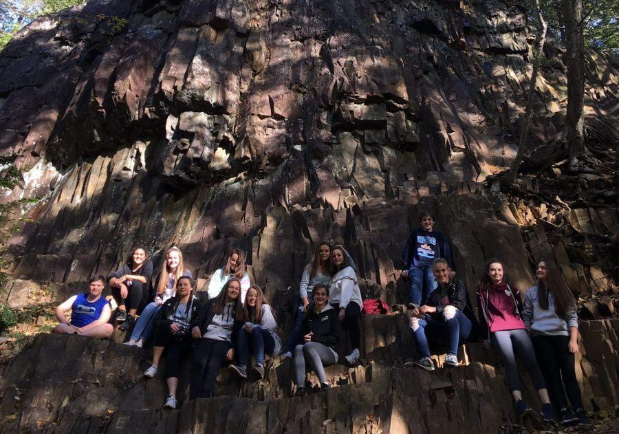 Students rest on a massive rock formation.