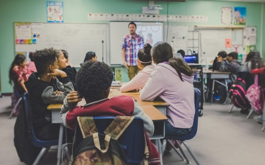 A typical elementary classroom with a teacher and students. However, some view the teacher as a shooter. neonbrand/ Unsplash